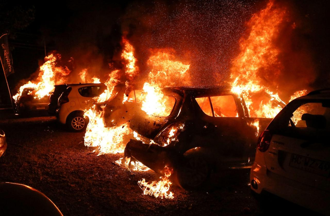 Cars are seen on fire during a protest against Chile's government in Vina del Mar