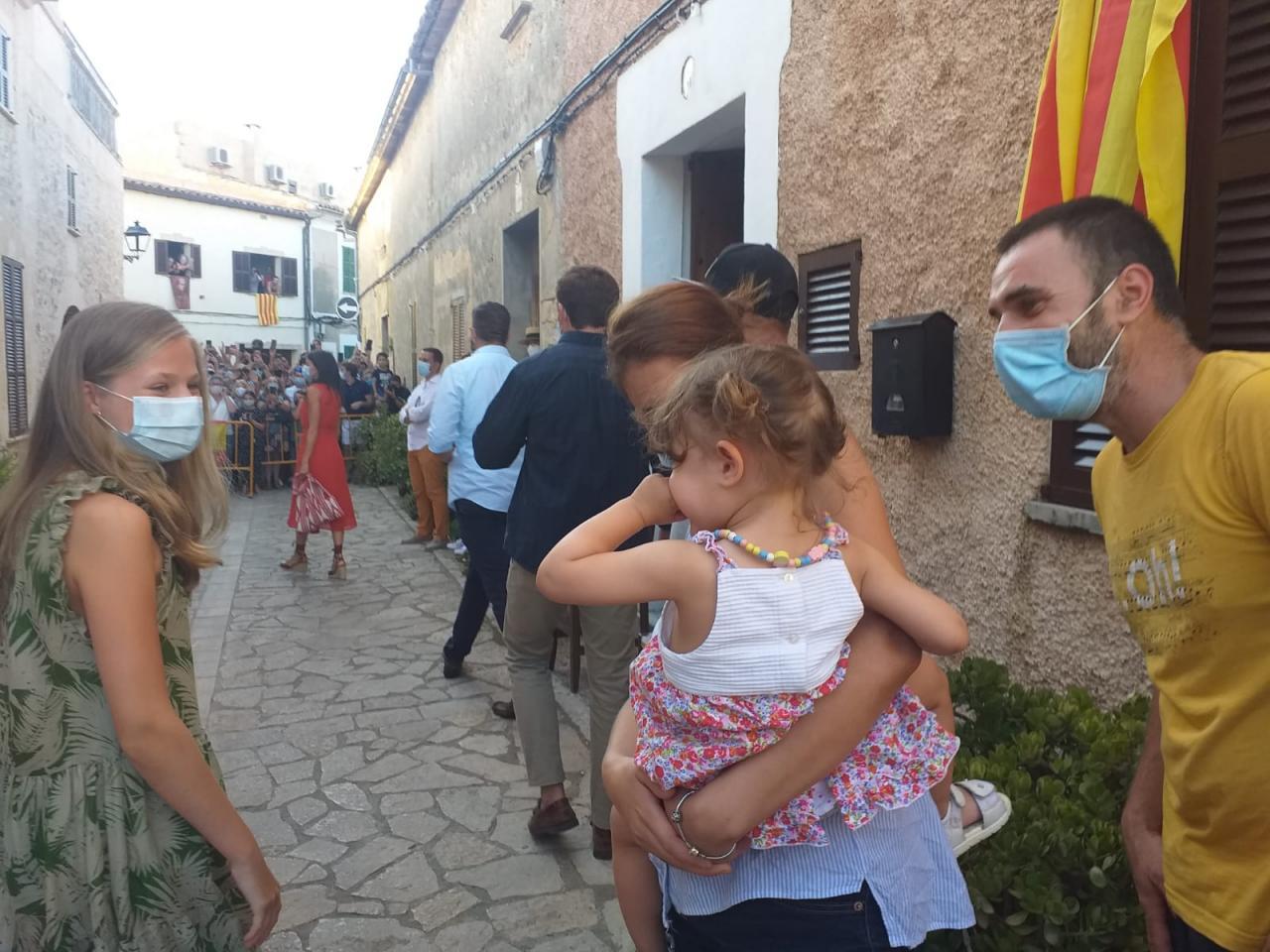 La Princesa de Asturias se ha detenido con una niña. Al fondo se ve la manifestación a favor de la Monarquía.