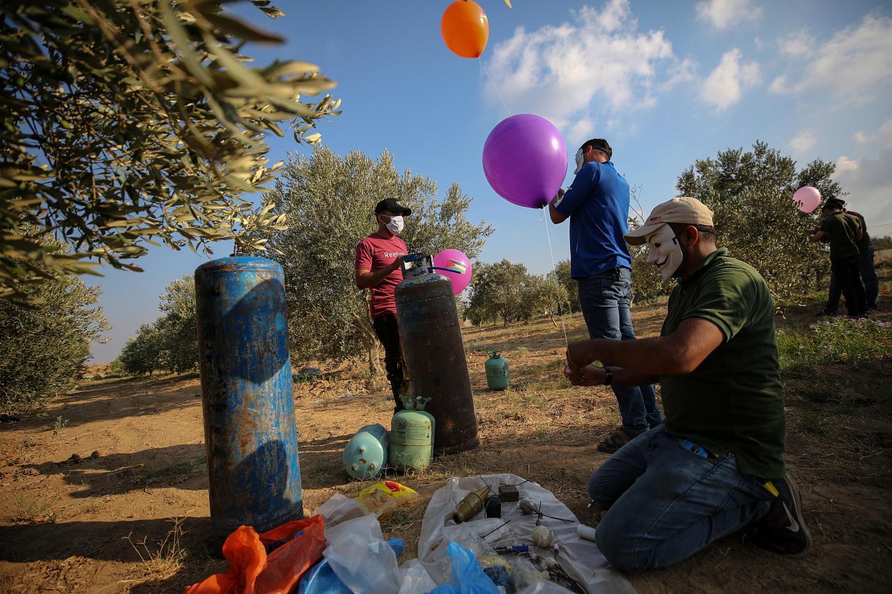 Palestinians prepare incendiary balloons at Gaza Strip