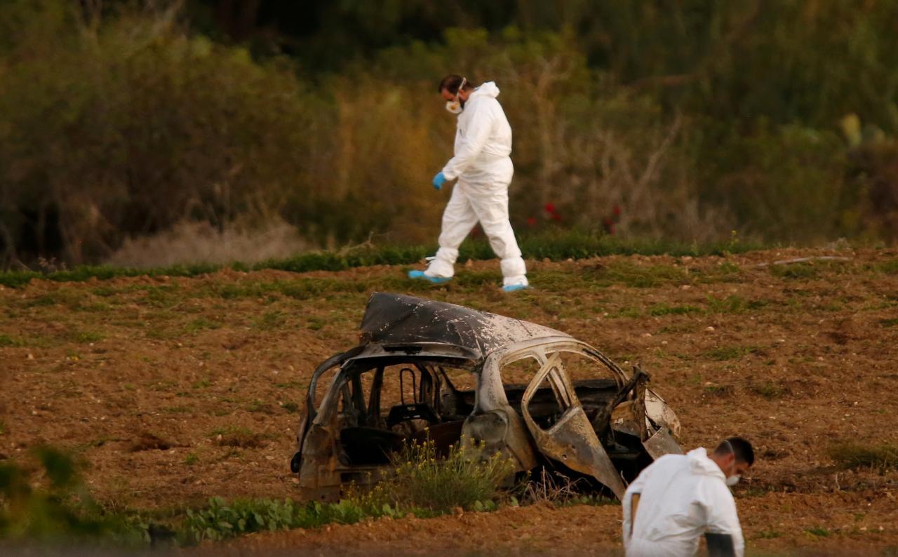 FILE PHOTO: Forensic experts walk in a field after a powerful bomb blew up a car killing investigative journalist Daphne Caruana Galizia in Bidnija