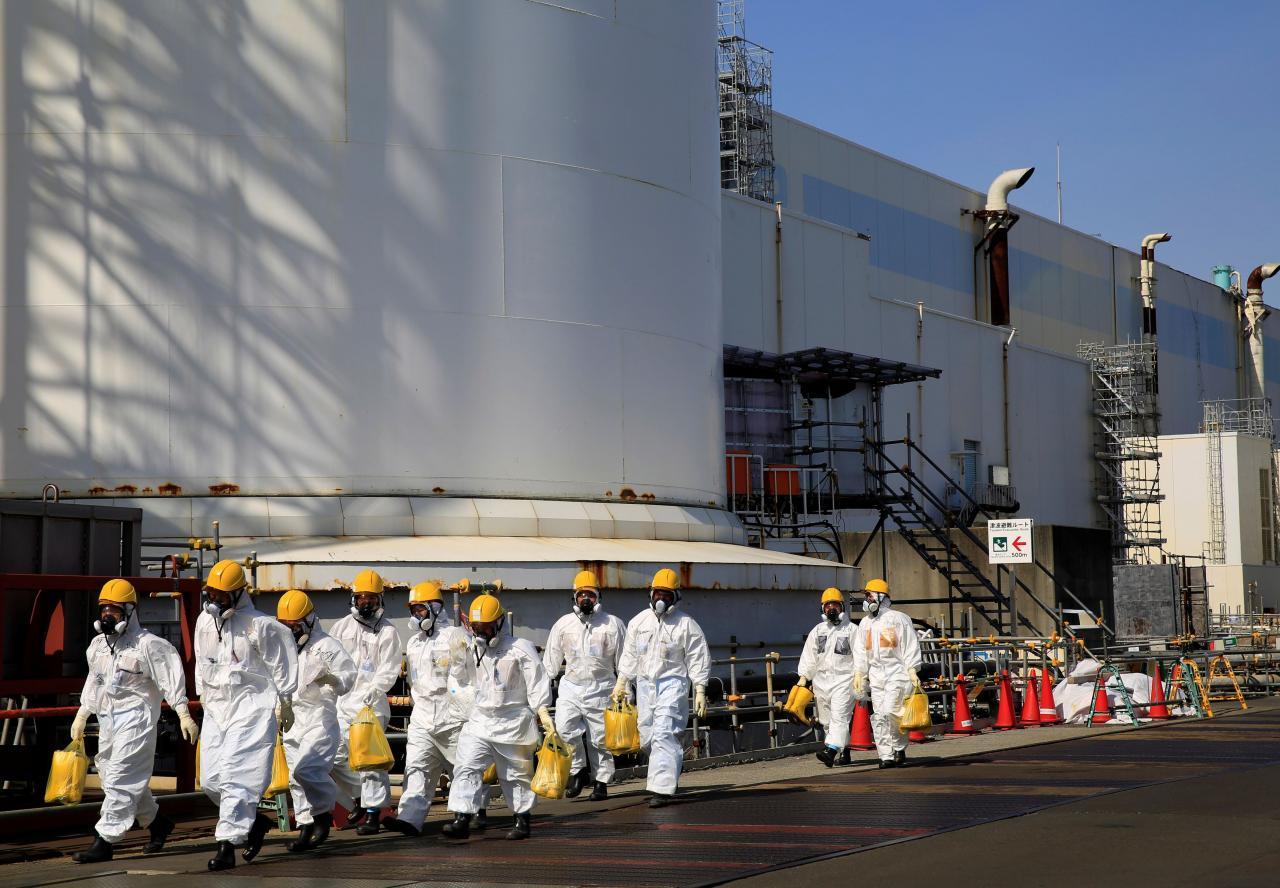 Workers walk near No. 2 and No. 3 reactor buildings at the tsunami-crippled Fukushima Daiichi nuclear power plant in Okuma town