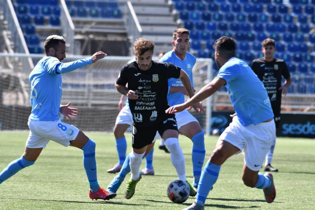 Colau, de la Peña, intenta avanzar con el balón ante la presión de varios jugadores de la UD Ibiza.