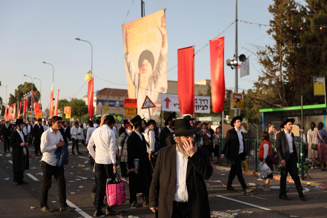 Jewish worshippers walk on Mount Meron