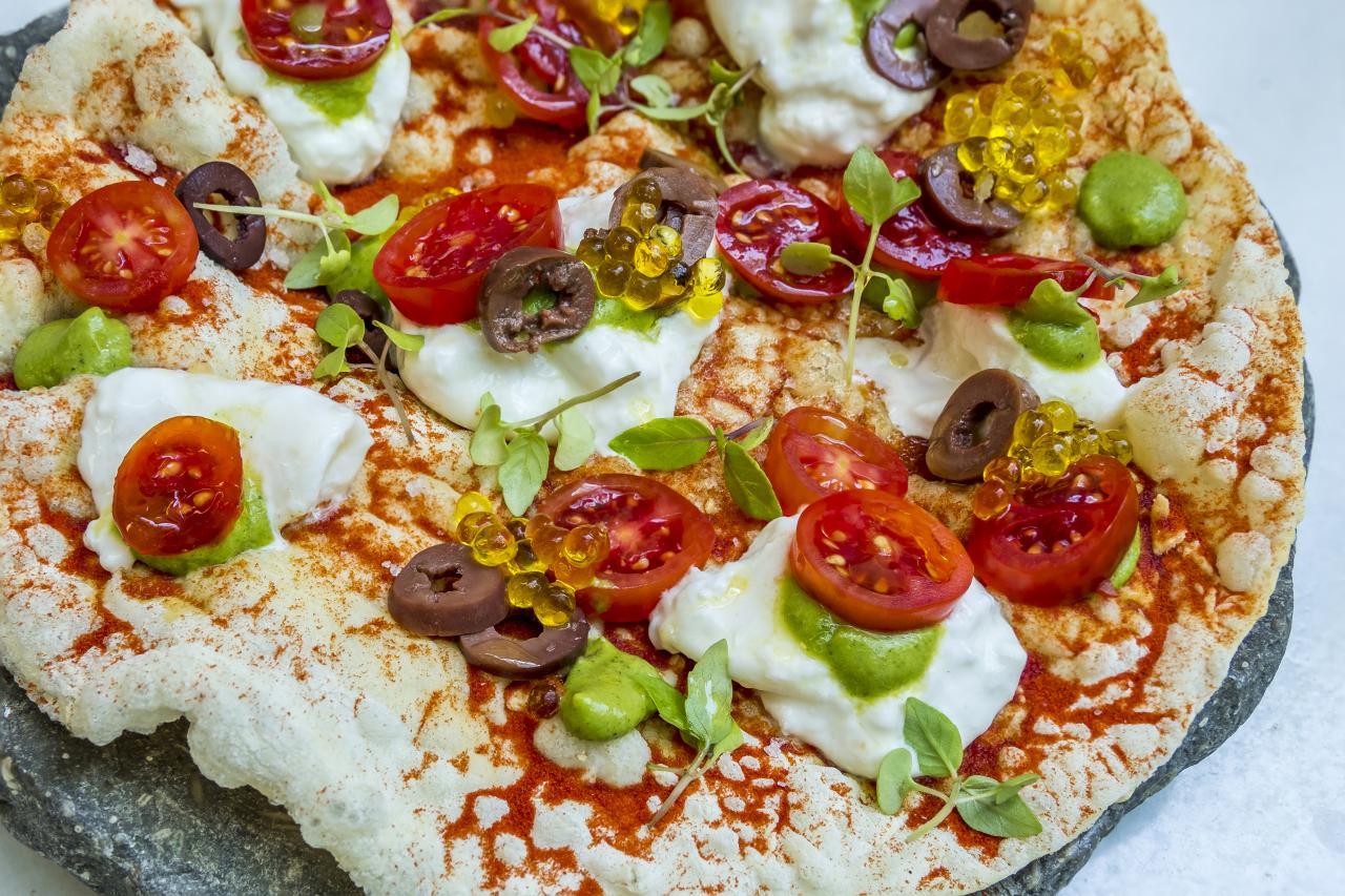 Pizza vietnamita, crujiente con abundante tomate sherry y albahaca sobre burrata Mozz'art de elaboración local.