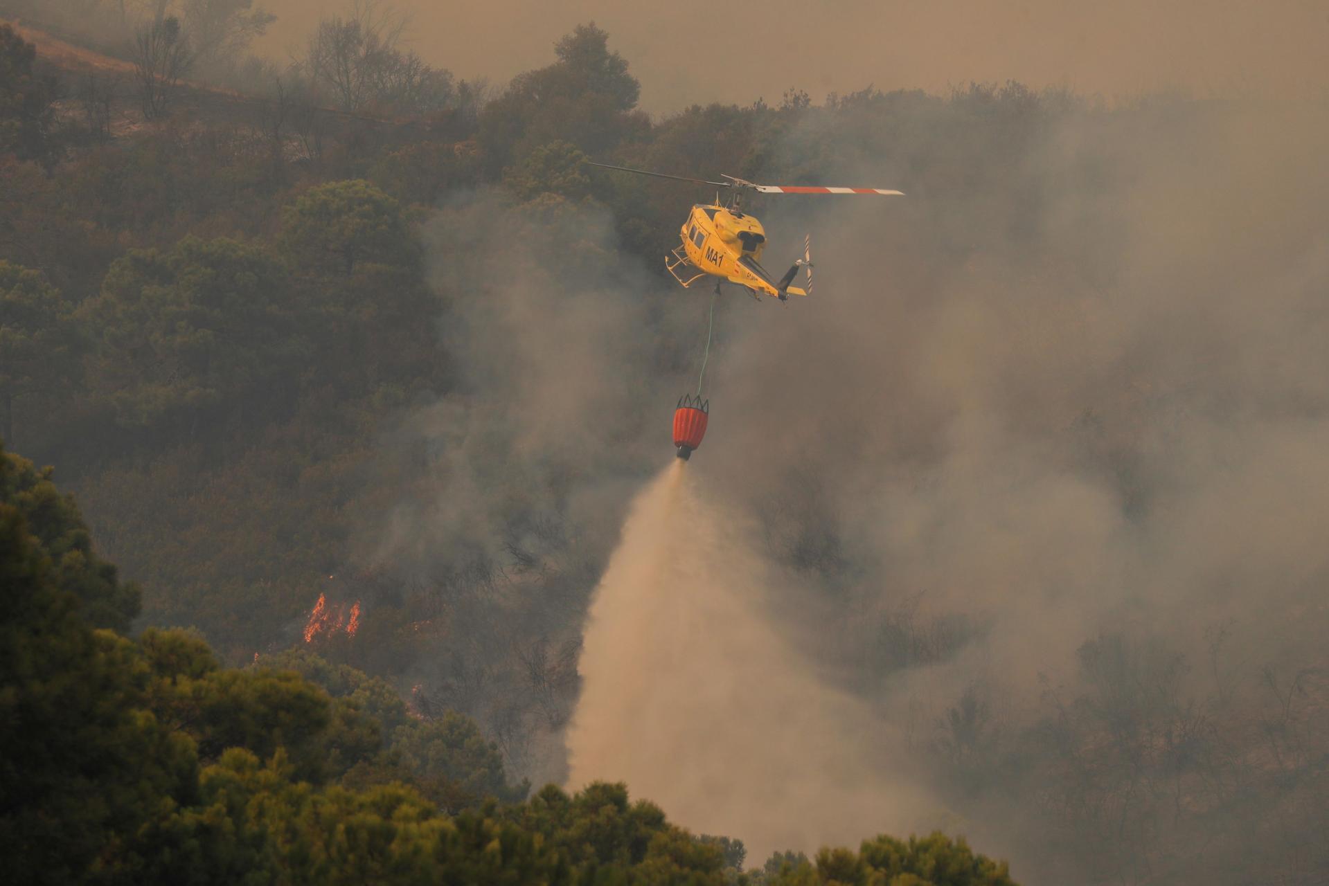 Firefighters battle wildfire burning on Sierra Bermeja mountain