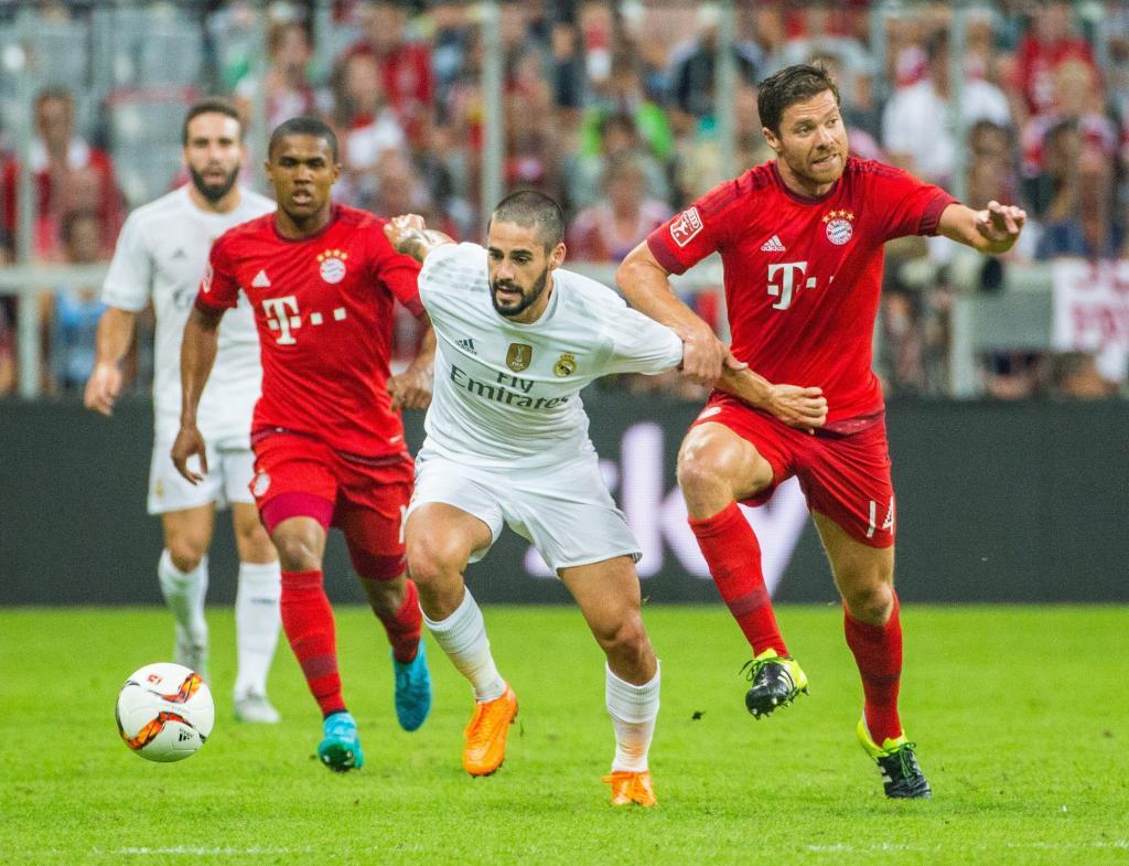 21bf651242 Los jugadores del Bayern Múnich Douglas Costa y Xabi Alonson disputan el  balón con Isco del