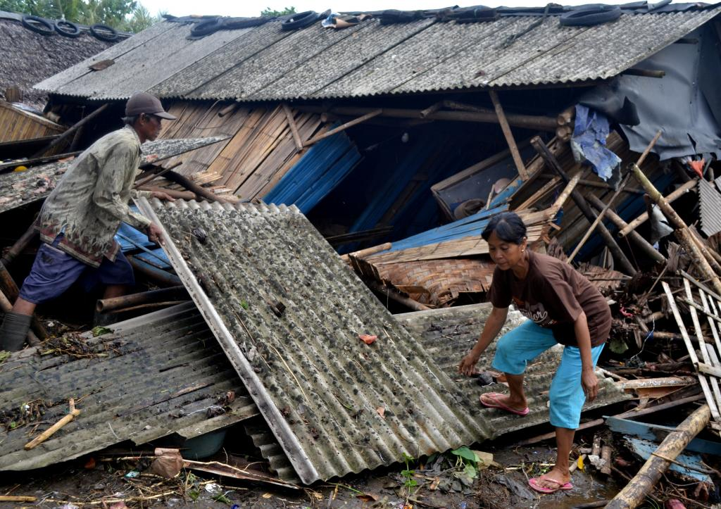 Residents collect debris from their collapsed house after it was hit by a tsunami at Panimbang district in Pandeglang, Banten pr