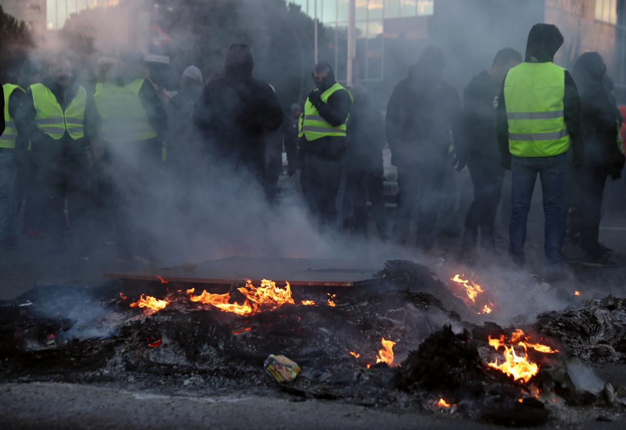 Taxi drivers stand next to a burning barricade during a strike against the regulation of ride-hailing and car-sharing services s