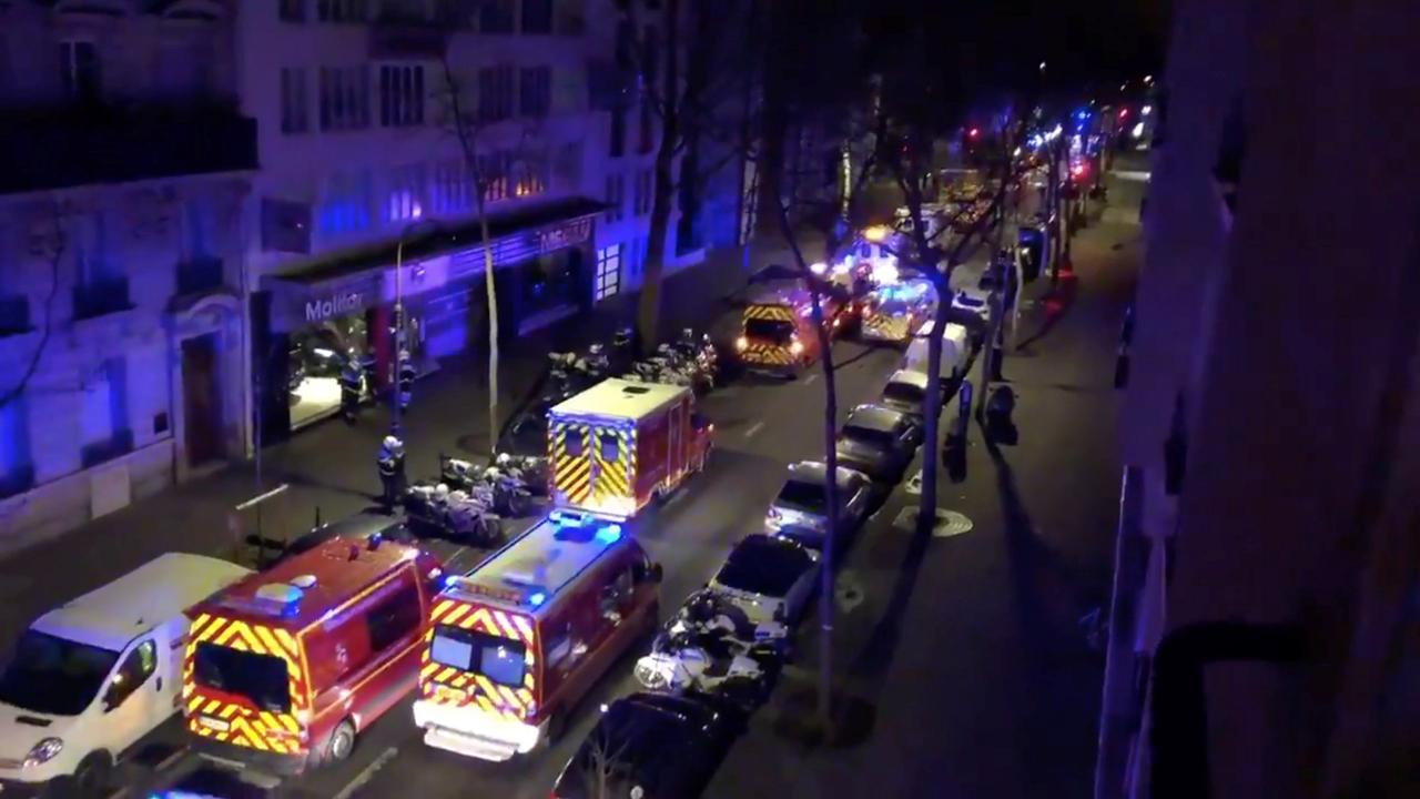 Emergency vehicles line a street where a residential building had caught fire in Paris
