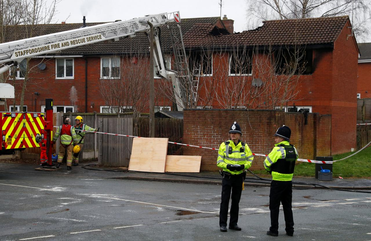Firefighters and police officers stand in front of a house partly destroyed by a fire in Stafford