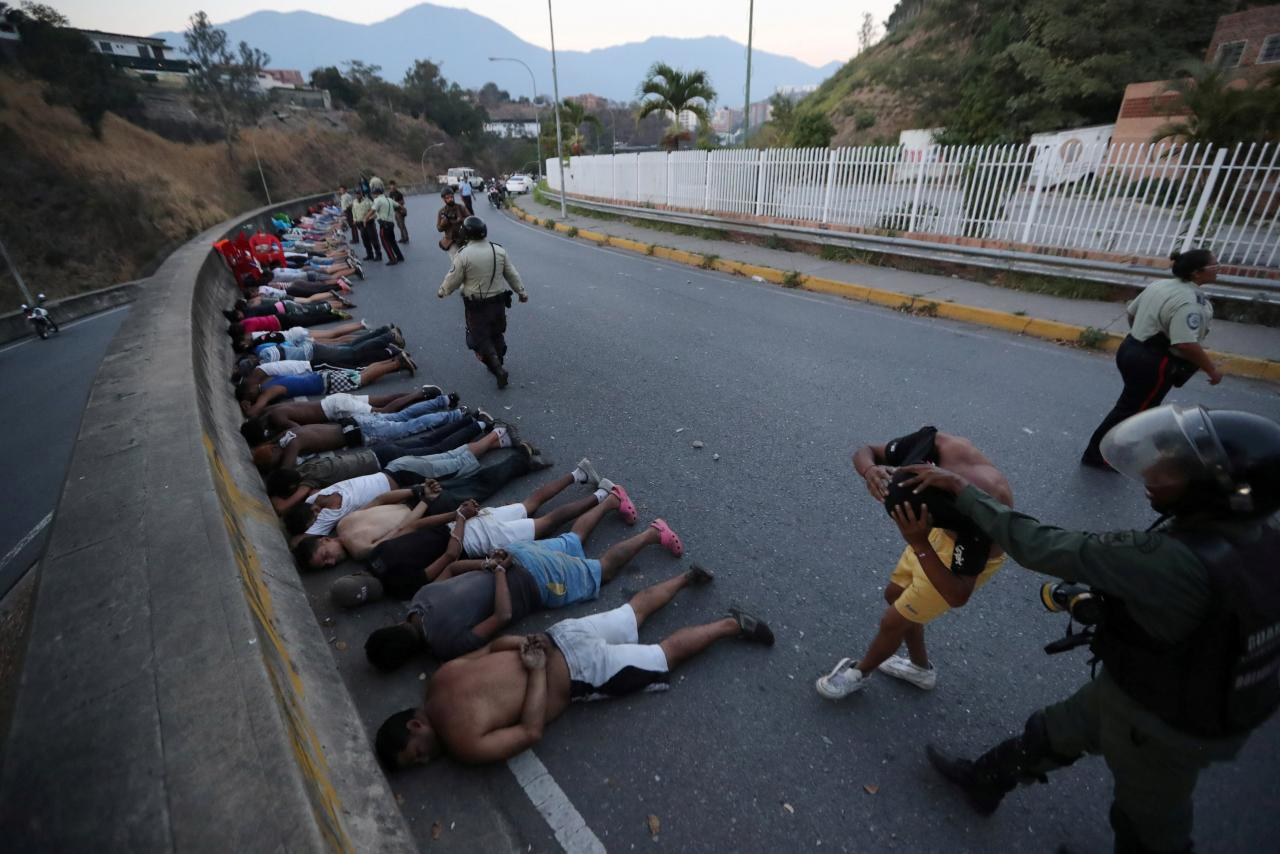 People detained by security forces lie on the street after looting broke out during an ongoing blackout in Caracas