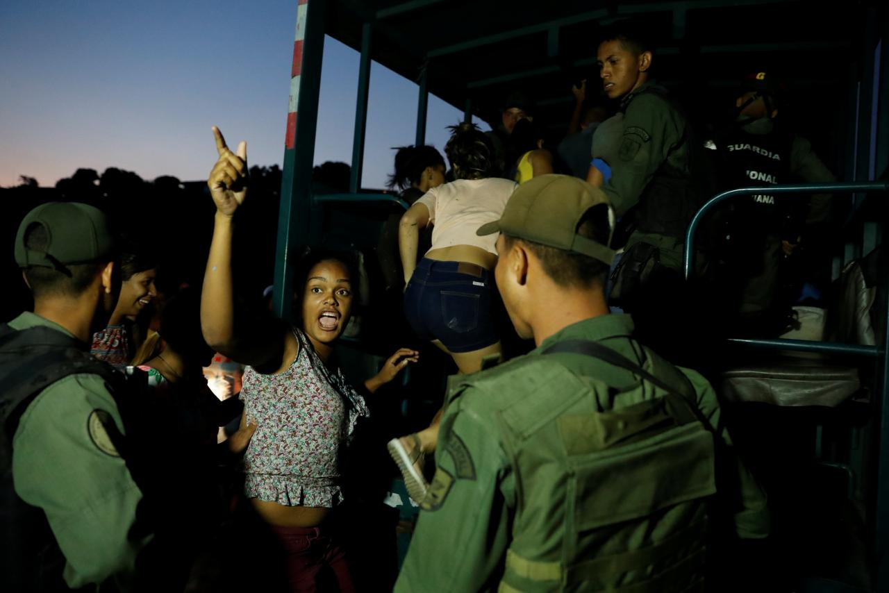 Detainees get on a truck after looting during an ongoing blackout in Caracas