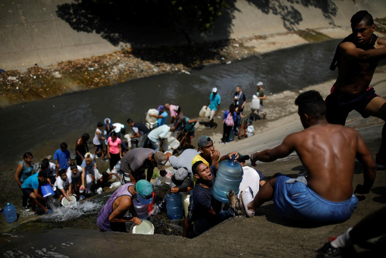 People collect water released through sewage drain that feeds into the Guaire River in Caracas