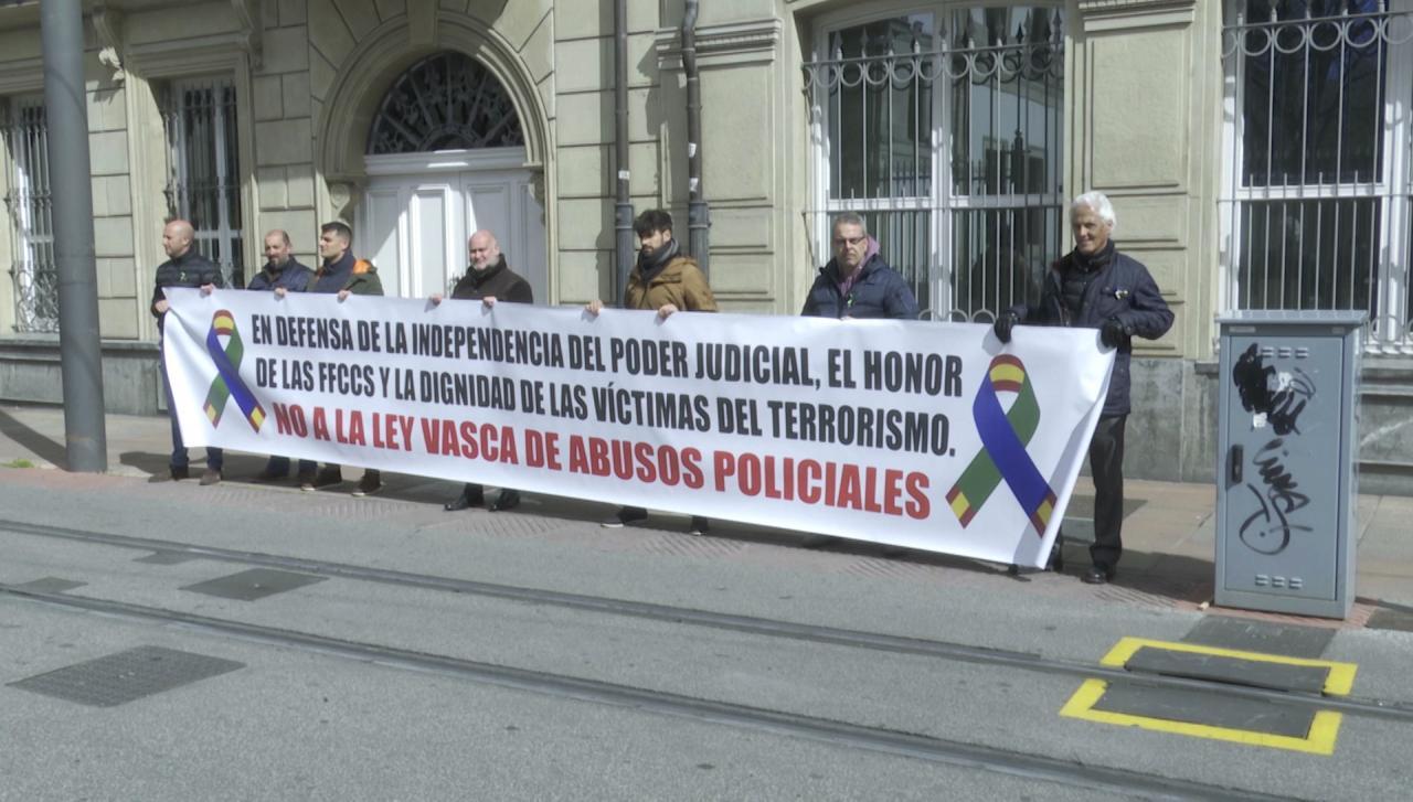 Representantes de sindicatos policiales durante la concentración ante el Parlamento Vasco, sujenatdo una pancarta en la que se