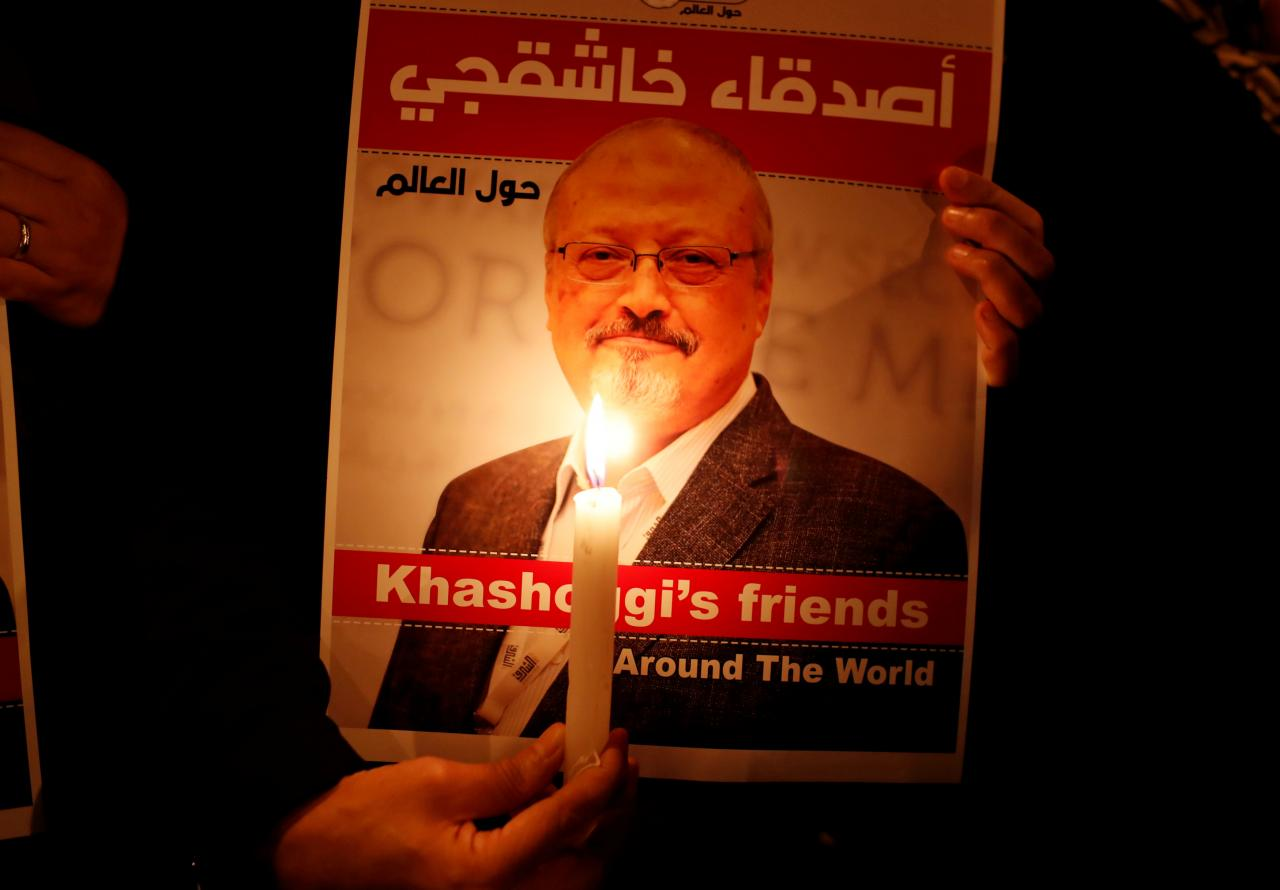 FILE PHOTO: A demonstrator holds a poster with a picture of Saudi journalist Jamal Khashoggi outside the Saudi Arabia consulate