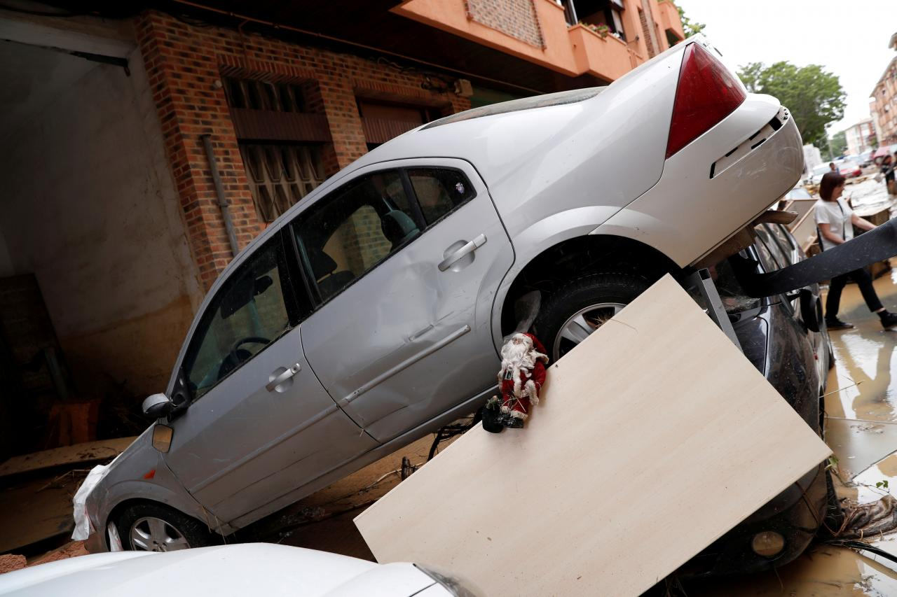 A Santa Claus lies on piled up cars and other debris after heavy rainfall in Tafalla