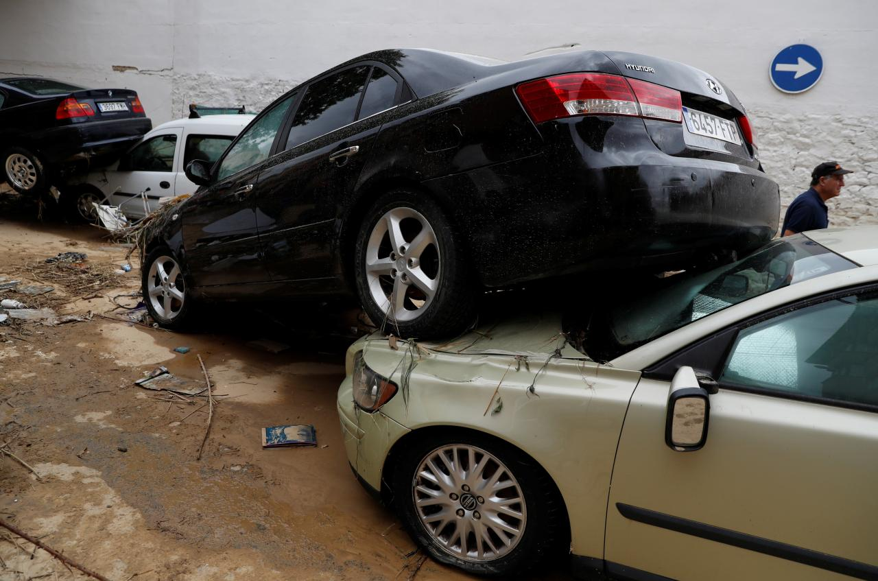 Man walks past damaged cars after heavy rainfall in Tafalla
