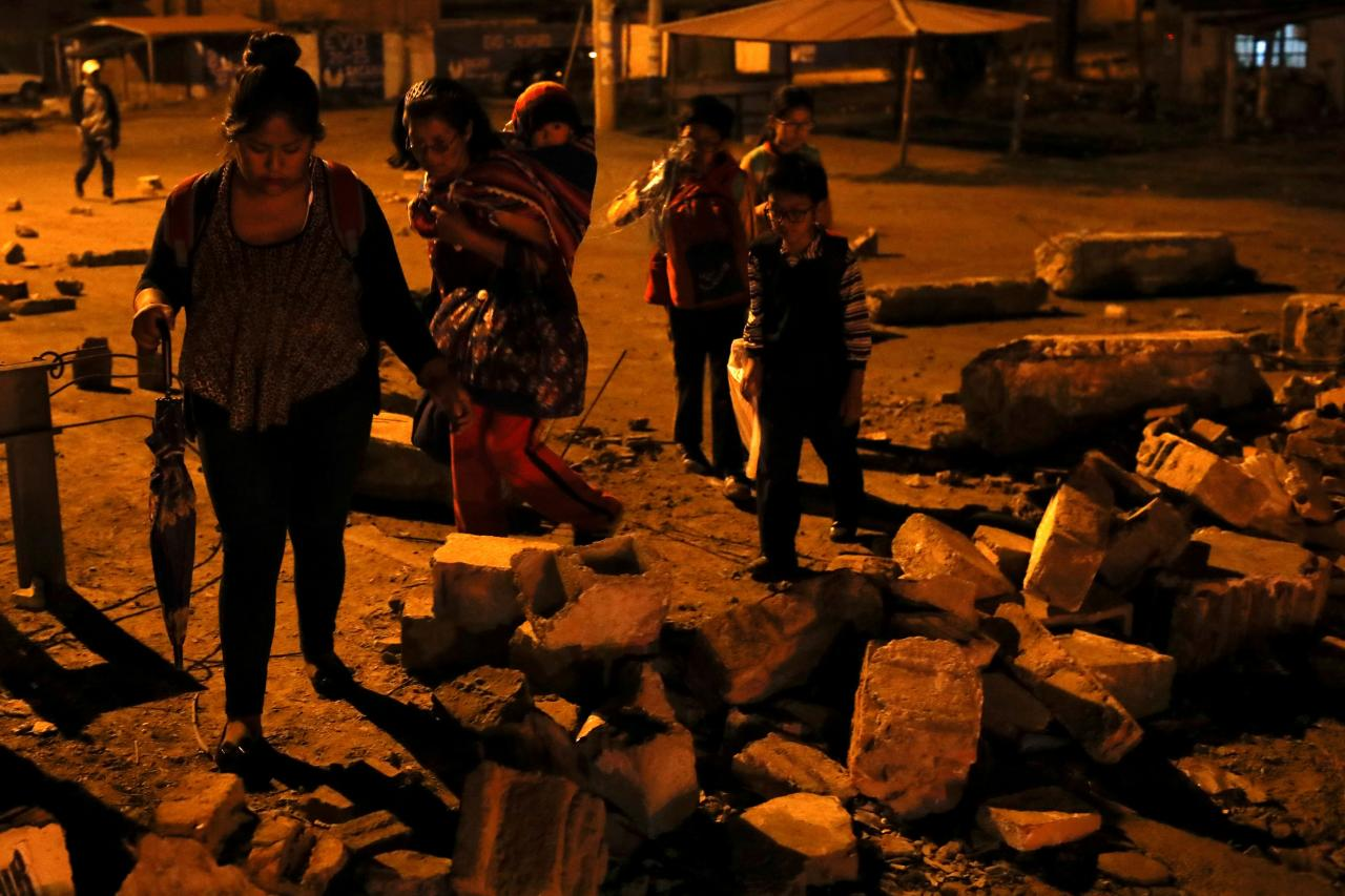 People walk through a barricade as coca farmers and supporters of Bolivia's ousted President Evo Morales stage a blockade of an entrance to Sacaba