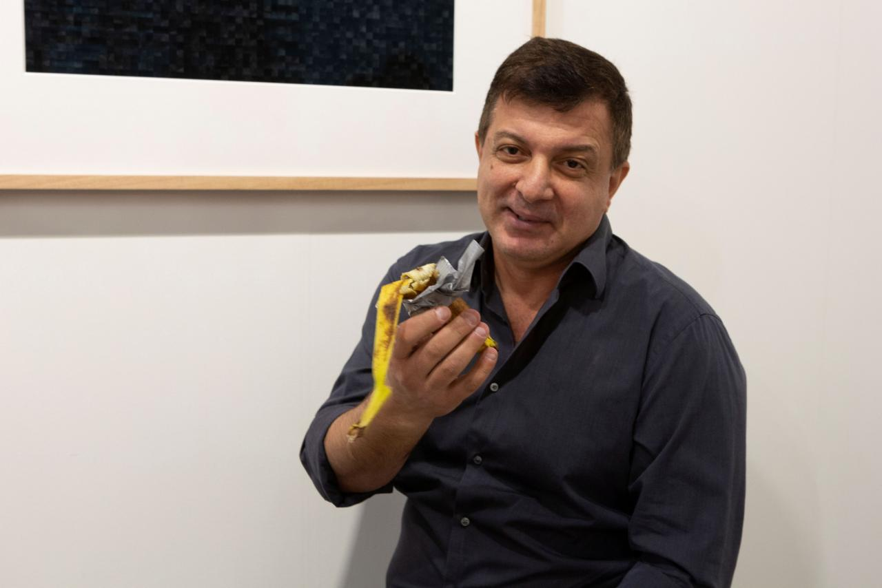 David Datuna shows the remains of the artwork 'Comedian' by the artist Maurizio Cattelan at Perrotin stand in Art Basel in Miami Beach