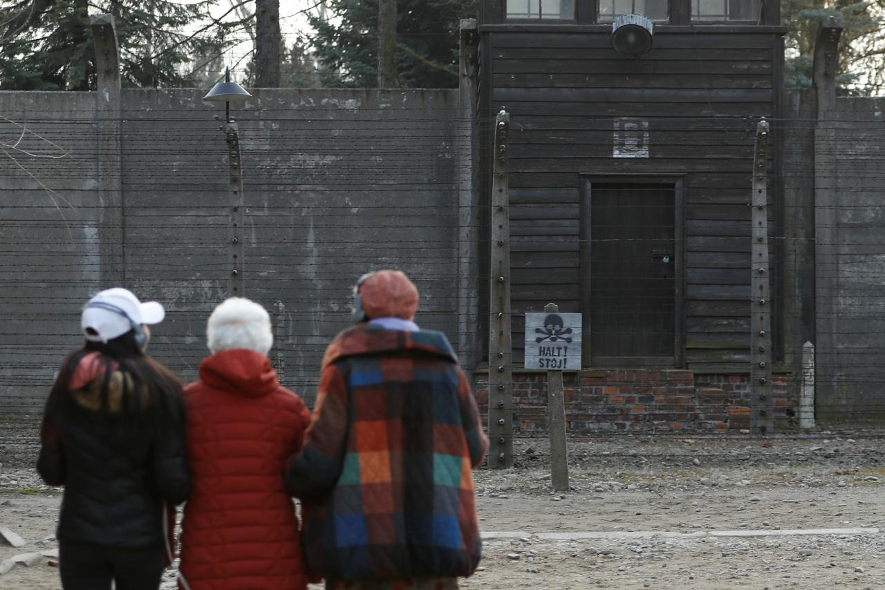 People walk in the Auschwitz museum a day prior to the 75th anniversary of the liberation of Nazi German concentration and extermination camp, Auschwitz