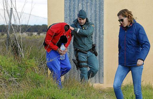 Dos agentes de la Guardia Civil custodian a Tòfol T. P. durante un registro.