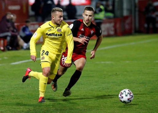 El defensa del Mirandés Enric Franquesa (d) pelea un balón con el centrocampista del Villarreal Javi Ontiveros durante el partido de cuartos de final de la Copa del Rey.