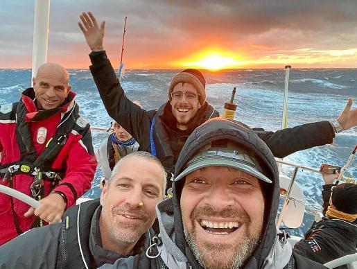Quique, con gorra y en primer plano, haciendo un selfi durante una puesta de sol, mientras Juan Lu Serra lleva el timón. A la derecha, vista desde el mástil.