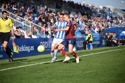 El jugador del Atlético Baleares Alberto Gil controla el balón ante la presión de un rival.
