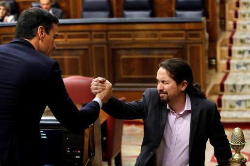 El líder de Unidas Podemos, Pablo Iglesias, saluda a Pedro Sánchez, tras su intervención ante el pleno del Congreso de los Diputados en la primera jornada de la sesión de investidura de Sánchez como presidente del Gobierno.