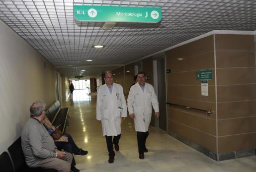 El doctor Javier Murillas y el doctor Jordi Reina, en el pasillo de acceso a la unidad de Microbiología de Son Espases.