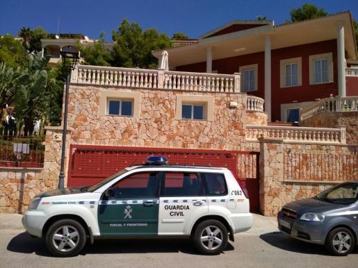 Un coche de la Guardia Civil, frente a una de las viviendas registradas.