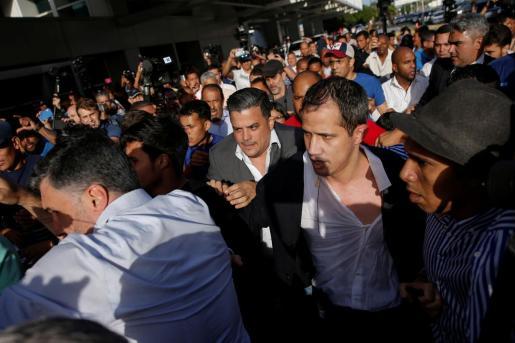 Juan Guaidó huyendo del numeroso grupo de chavistas que le ha golpeado a su llegada al aeropuerto.