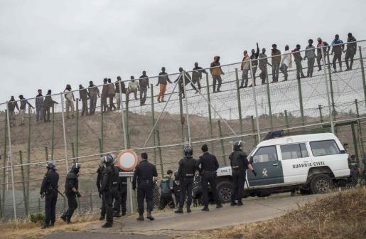 Inmigrantes encaramados a la valla de Melilla, en una imagen de archivo.