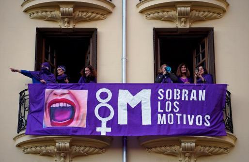 Mujeres en un balcón con una pancarta del Día Internacional de la Mujer.