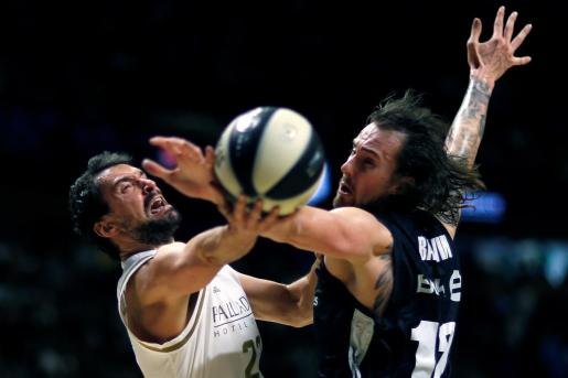 El base del Real Madrid Sergio Llull (i) lanza a canasta defendido por el checo Ondrej Balvin, del Bilbao Basket.