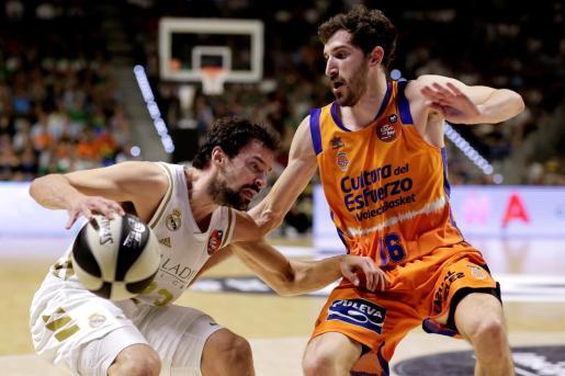 El jugador menorquín del Real Madrid, Sergio Llull, con el balón ante el jugador de Valencia Basket, Guillem Vives, durante el primero de los dos partidos de semifinales de la Copa del Rey, que se disputa en el Palacio de Deportes José Mª Martín Carpena, Málaga.