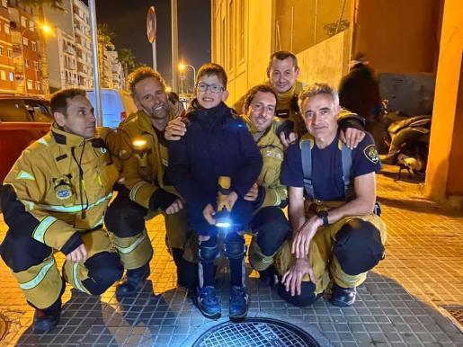 El pequeño Ángel juntoa a un grupo de bomberos