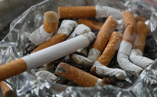 Un cenicero repleto de cigarrillos.
