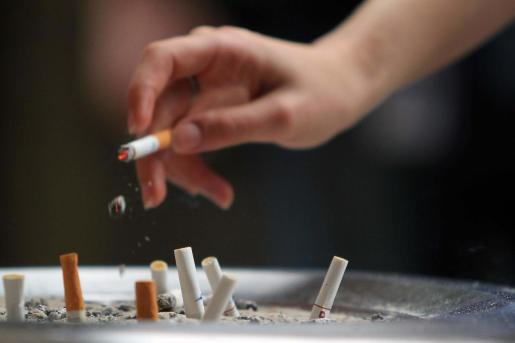 Un fumador deposita la ceniza de su cigarro en un cenicero.