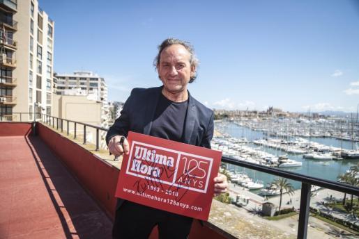 El diseñador catalán sosteniendo un cartel del 125 aniversario de Ultima Hora con su firma estampada.
