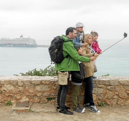 Una familia de cruceristas se fotografía en Dalt Vila con un crucero atracado en el dique de es Botafoc de fondo.
