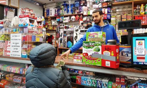 El joven Ahmed Alwan trabaja en el supermercado de su familia en el barrio neoyorquino del Bronx.