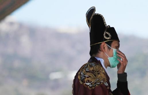 Un hombre vestido con ropa tradicional se cubre la boca con una mascarilla en Corea del Sur