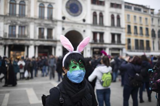 Una mujer, con mascarilla, en Venecia.