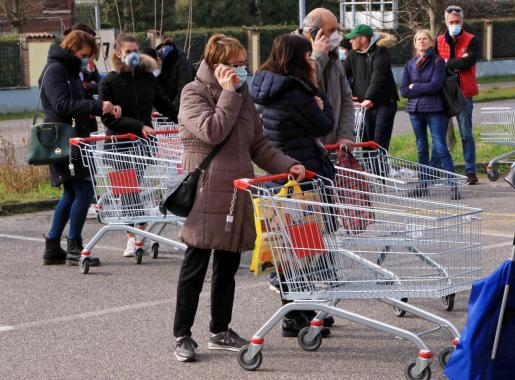 Ciudadanos, con mascarilla, en el exterior de un supermercado en Casalpusterlengo, en Italia.