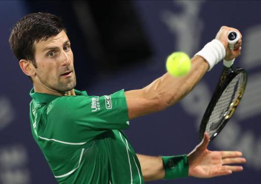 El tenista serbio Novak Djokovic se dispone a golpear la bola durante su estreno en Dubai.