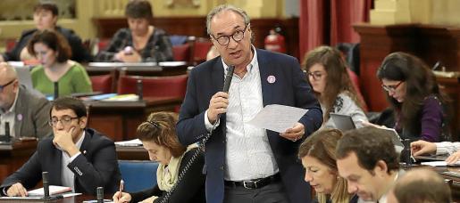 El conseller d'Educació, Martí March, en un pleno. Detrás, dos diputadas de Podemos.