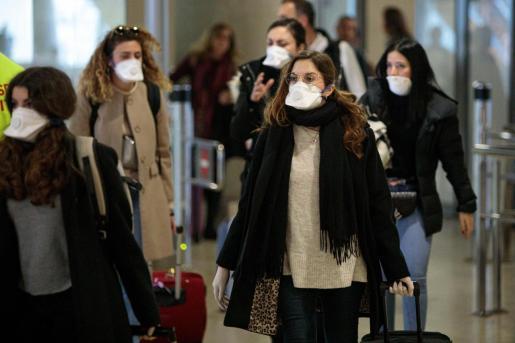 Viajeros procedentes de Italia protegidos con mascarillas.