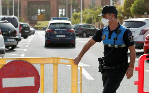Local police officer pushes a barrier to block the entrance of H10 Hotel, which is on lockdown after novel coronavirus has been confirmed in Adeje, on the Spanish island of Tenerife, Spain February 25, 2020. REUTERS/Borja Suarez CHINA-HEALTH/SPAIN