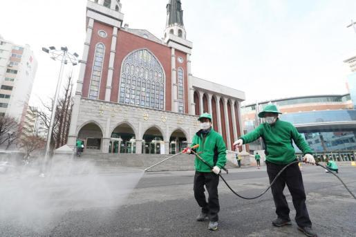 Trabajadores desinfecta una zona pública de Seul.